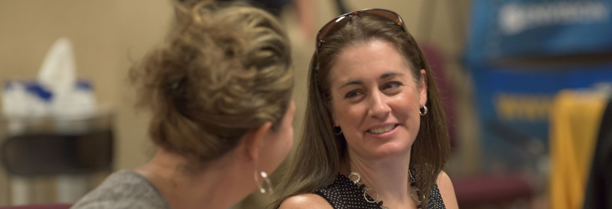 Woman smiling at colleague during a CE session