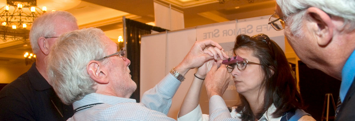 Woman being fitted for a visual device during vendor expo at Envision Conference
