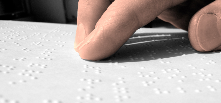 Photo of a hand reading Braille