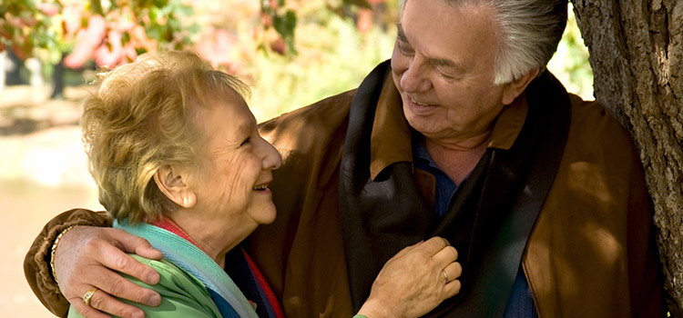 Elderly couple under tree smiling